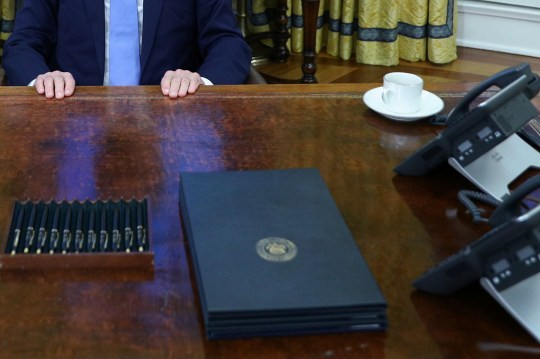 U.S. President Joe Biden rests his hands on the Resolute Desk before signing multiple executive orders inside the Oval Office of the White House in Washington