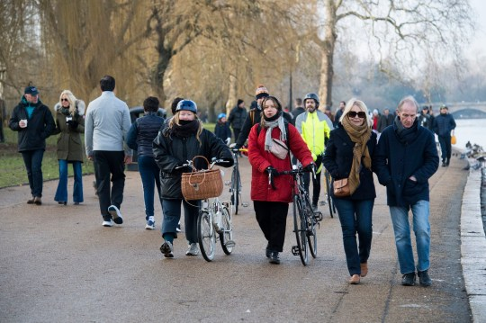 People walk next to the Serpentine in Hyde Park