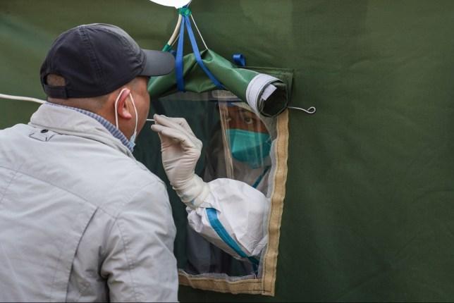 Un travailleur médical recueille un échantillon sur écouvillon d'un résident sur un site de test COVID-19 dans le district de Daxing à Pékin, capitale de la Chine, le 26 janvier 2021.