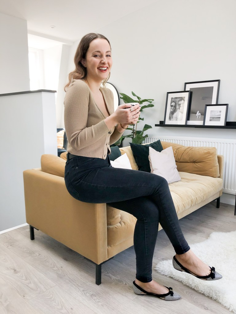 What I Rent: Annabel, two-bedroom flat in Angel, Islington - Annabel sitting on the edge of her sofa