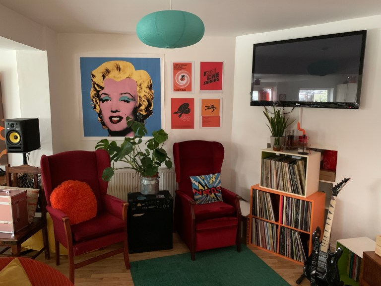 What I Rent: Iona and Jack, Oldham, Manchester - two red chairs in the living room in front of large tv, records, and a guitar