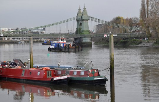 Houseboats are seen moored near to Hammersmith Bridge, the closure of which has caused the annual Oxford versus Cambridge boat race on the River Thames, which passes under the now structurally dangerous Victorian bridge, to be relocated outside of London for the first time since World War Two, London, Britain, November 26, 2020. REUTERS/Toby Melville