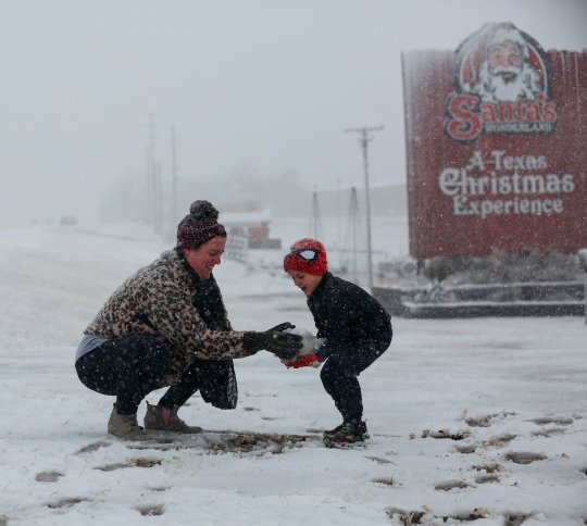 Heather makes a snowball and hands it to her son, Weston, 5, to build a snowman at Santa's Wonderland on Highway 6 Sunday, Jan. 10, 2021, in College Station, Texas. The family of five drove up from Waller to find snow. (Yi-Chin Lee/Houston Chronicle via AP)