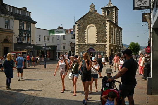 People walk through the streets in Keswick in the Lake District in north west England on August 14, 2020, as many people take advantage of the seasonal weather to holiday at home rather than take the risk of having to self-isolate for two weeks on return from a foreign holiday.