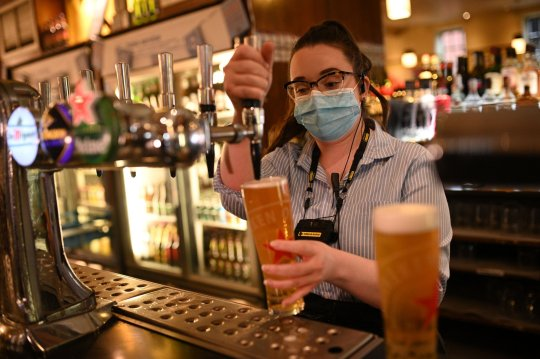 A member of the bar staff pulls a pint in a Wetherspoons pub in Leigh, Greater Manchester, northwest England on October 22, 2020 ahead of new coronavirus restrictions coming into force in the area. - British Prime Minister Boris Johnson imposed tougher coronavirus restrictions on an area of the northewest of England after placing Greater Manchester into the government's tier 3, the highest coronavirus alert level, defying local leaders who bitterly opposed the move without extra funding. The extra restrictions which servely limits social mixing in hospitality venues will come into effect on October 23, 2020. (Photo by Oli SCARFF / AFP) (Photo by OLI SCARFF/AFP via Getty Images)