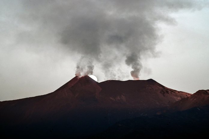 CATANIA, ITALY - FEBRUARY 28: The full moon having just set, is visible, behind Etna's smoking summit craters on February 28, 2021 in Catania, Italy. The shots were taken thanks to coordinates provided by astrophysicist Massimo Cecconi of the Galileo National Telescope in La Palma, Canary Islands, Spain. Etna, Europe's highest active volcano and one of the world's most active volcanoes, has in recent weeks experienced numerous paroxysms with ash emissions from its south-east crater. (Photo by Fabrizio Villa/Getty Images)