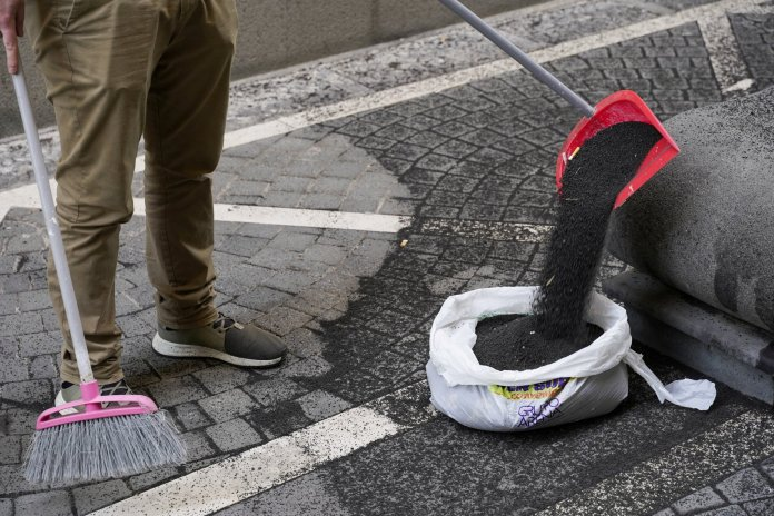 A person sweeps volcanic ash from Mount Etna on a street in Giarre, Italy, February 28, 2021. REUTERS/Antonio Parrinello