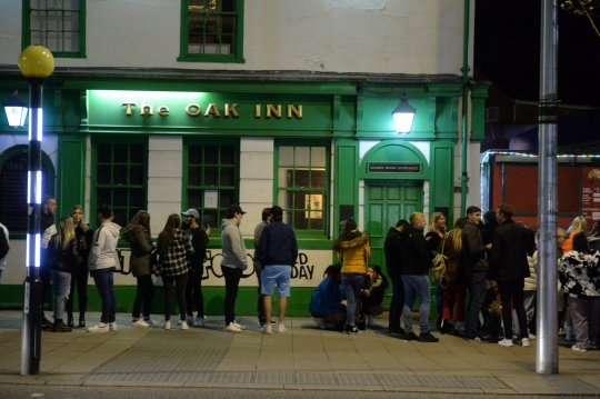 People line up outside The Oak Inn in Coventry, hoping to enjoy their first pints after the lockdown moments after midnight as restrictions across the UK are partially relaxed.  The establishment is licensed until 6 a.m. and also plans to sell food all night long, such as pizzas, burgers, and kebabs.  April 11, 2021.