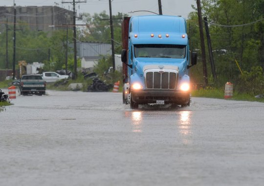 A truck moves along a flooded Old Gentilly highway as inclement weather passes through the New Orleans metro area on Tuesday, April 13, 2021.