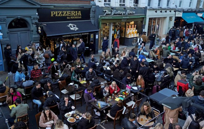 People sit at tables outside to eat and drink in reopened bars and restaurants