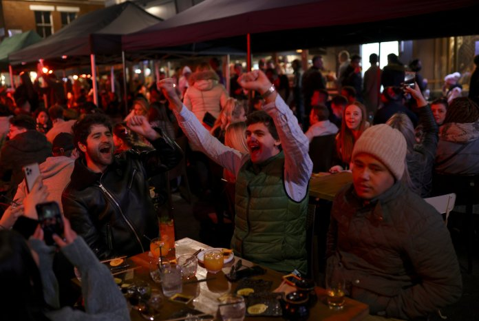 People applaud at a table in Soho.  The British rushed to take advantage of the first weekend since the pubs opened in sunny spring.