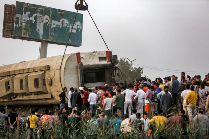 People watch a telescopic railroad crane lift an overturned passenger car at the scene of a train crash in the city of Toukh, in Egypt's central Nile Delta province of Qalyubiya on April 18, 2021. - The train crash in Egypt left 97 injured on April 18.  after it derailed from its tracks on its way north from the capital Cairo, the health ministry said, during the latest rail disaster.  Eight cars derailed tracks as the train headed for Mansoura, about 130 kilometers north of Cairo.  (Photo by Ayman AREF / AFP) (Photo by AYMAN AREF / AFP via Getty Images)