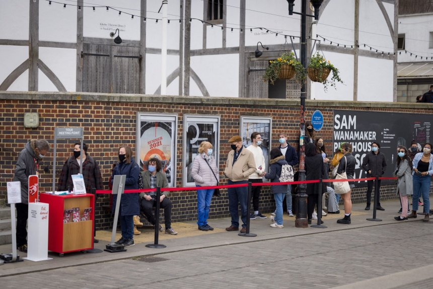 Members of the public, wearing face coverings due to Covid-19, queue for a guided tour of Shakespeare's Globe theatre in London on April 14, 2021. - Following the UK's massive vaccine rollout, non-essential retail such as clothes shops, and hospitality including restaurants and pubs, reopened their doors across England on April 12.