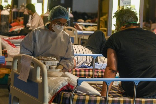 A health worker wearing personal protective equipment (PPE kit) distributes food to Covid-19 coronavirus patients inside a banquet hall temporarily converted into a Covid care centre in New Delhi on May 7, 2021. (Photo by Prakash SINGH / AFP) (Photo by PRAKASH SINGH/AFP via Getty Images)