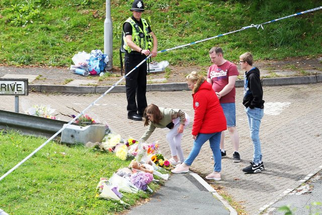 Members of the public place flowers at Royal Navy Avenue on August 15, 2021 in Plymouth, England. Police were called to a serious firearms incident in the Keyham area of Plymouth on Thursday evening where lone gunman, named by police as Jake Davison, 22, shot and killed five people before turning the gun on himself.