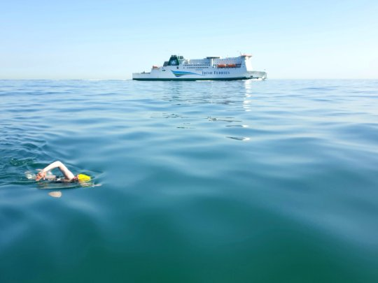 Chloë McCardel swimming in the channel with ferry in background