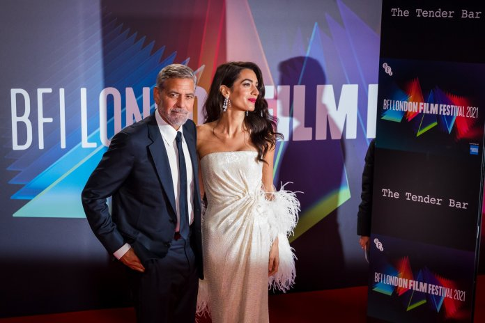 US Director George Clooney (L) and his wife lawyer Amal Clooney attend the UK premiere of 'The Tender Bar' during the BFI London Film Festival at the Royal Festival Hall