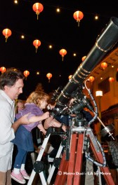 a small girl is held up to a telecrope so she can look at the moon