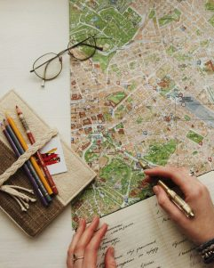 Person using a pencil to draw on a map