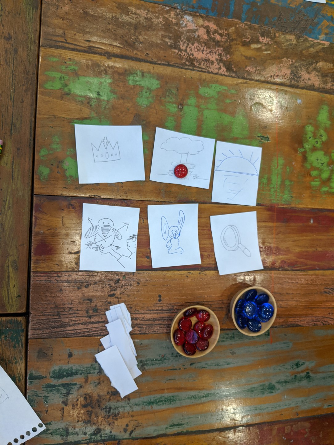 Players use these images as prompts for their story. Players place blue tokens on pieces of the story they liked and red on ones they didn't! Blue tokens are points to the person who corresponds to that image