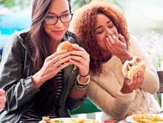 Foto mostra duas jovens comendo hamburger ilustrando lançamento da Cargill