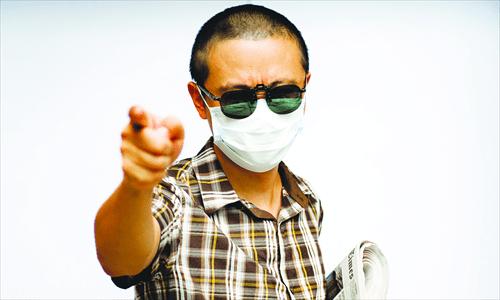 El periodista ciudadano Zhou Xiaoyun cubre su rostro porque asegura que tiene varios enemigos que le gustarían verlo muerto /Foto facilitada por Zhou al diario Global Times.