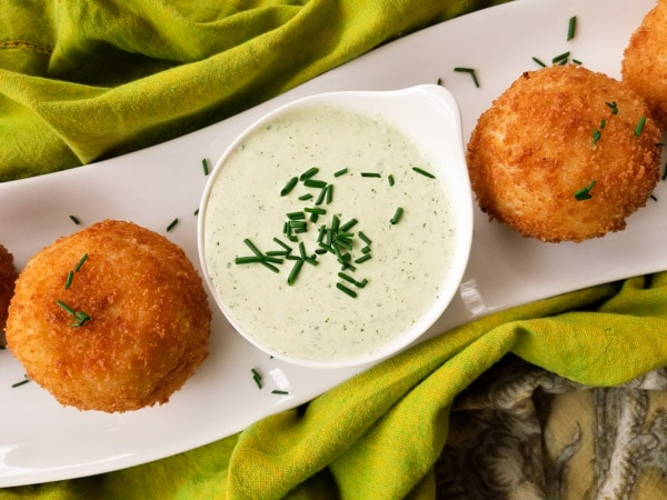 Rellenos de Papa (Stuffed Potato Balls), are stuffed with a savory picadillo or beef ground meat and fried leaving a crusty balance and perfectly moist on the inside served with a poblano dipping sauce.