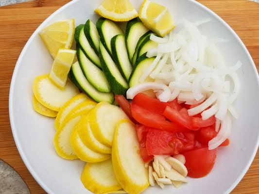 Zucchini, yellow squash, onions, tomatoes, garlic and lemon wedges for the Tilapia en Papillote Packets (Tilapia in Parchment Packets).