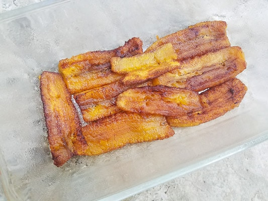 A layer of plantains in a meatloaf casserole for the pastelón.