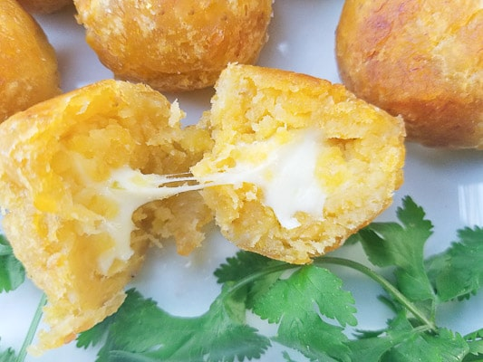 Bolón de Verde cut in half with creamy delicious melted cheese flowing out.