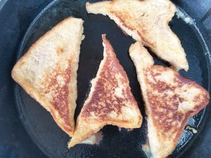 Cooked dulce de leche french toast in a skillet.