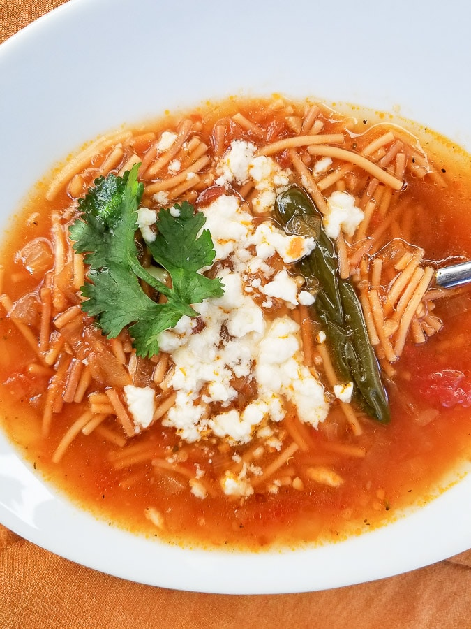 Sopa de Fideo served in a white bowl and topped with queso fresco and fresh cilantro.