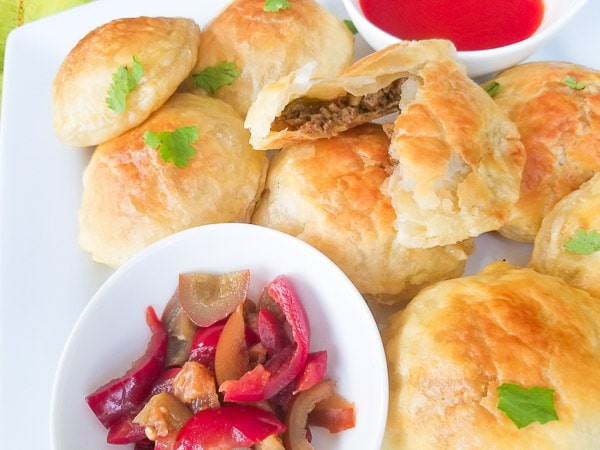 Pastelitos de Carne (Puff Pastry with Meat Filling) served with a side of hot sauce and cherry peppers on a large white platter.