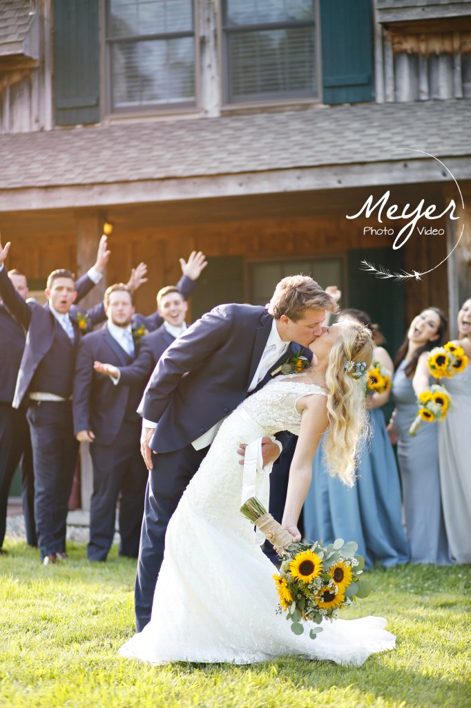 posing in front of bridesmaids and groomsmen