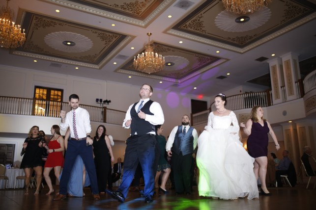 the bride dancing with family and friends at the carriage house