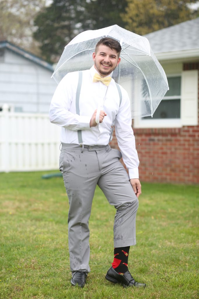 groom standing under clear umbrella at a wedding in NJ