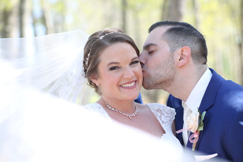 groom kissing bride at wedding in 2019