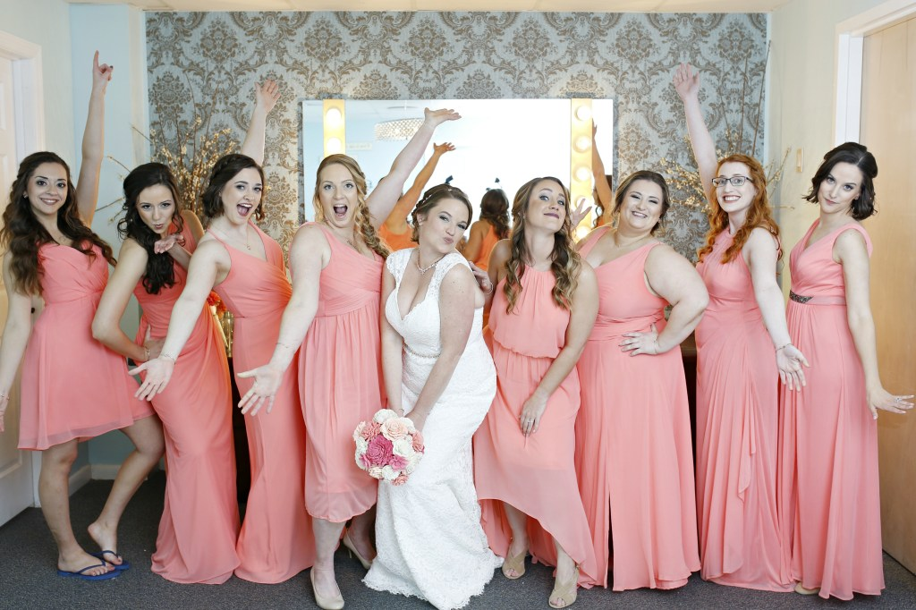 bridesmaid with bride standing in front of a mirror at a wedding in 2019