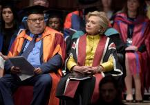 US politician Hillary Rodham Clinton, right, sits in the Great Hall at Swansea University, prior to receiving an Honorary Doctorate in recognition of her commitment to promoting the rights of families and children around the world, in Swansea, Wales, Saturday, Oct. 14, 2017. (Ben Birchall/PA via AP)