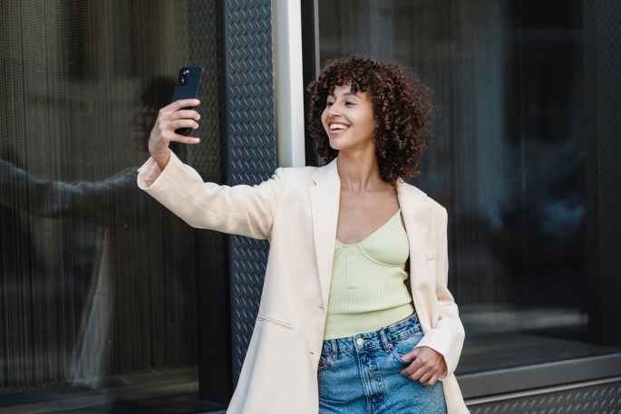 positive ethnic woman taking self portrait on smartphone in town