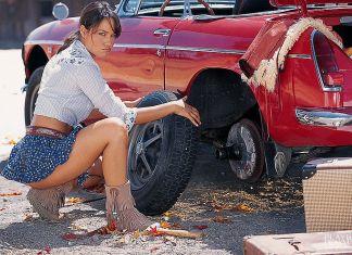 Cara Zavaleta changing the tire on an MG MGB