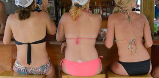 Three women drinking in bikinis at The William Thornton Floating Bar and Restaurant, The Bight, Norman Island, British Virgin Islands