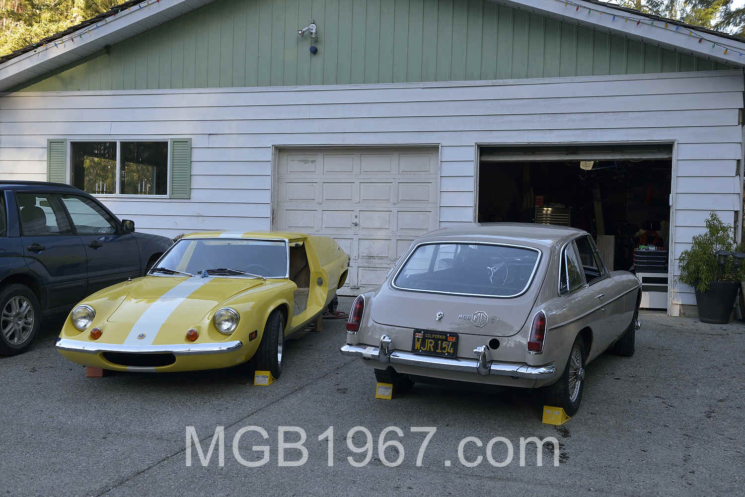 Lotus and MGB in front of garage
