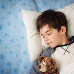 Young boy sleeping on bed with teddy bear