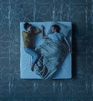 Couple lying in bed, top view