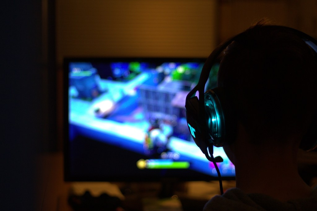 Person playing video games with a headset as an illustration of gaming disorder.
