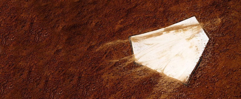 Image of home plate at a baseball field partially covered in dirt