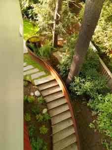 """We created steps down a steeply sloping backyard using a framework of self-weathering steel that holds in peastone treads. To the right is a steel handrail that holds water, we call it a handrill."" p. 135. Photo © Susan Teare"