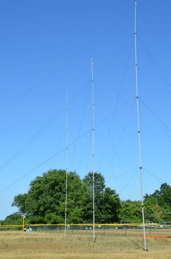 Three Masts setup with Ground Mounts in a field as supports for a mobile dipole antenna system