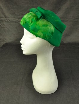 "Women's felt hat in emerald green ""styled by Michele"" on label at back. Flatish style, with shallow crown wider brim. Well stitched matching band with bow at front and front of brim covered with matching emerald green feathers"